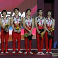 The Japan men's gymnastics team, including legend Kohei Uchimura (right), stands on the podium after earning the bronze medal in the team event at the world championships in Doha on Monday. | AP