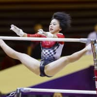 Mai Murakami competes in the uneven bars portion of the women's all-around team event at the World Artistic Gymnastic Championships in Doha on Tuesday. | KYODO
