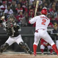 Hawks catcher Takuya Kai throws out Carp base runner Takashi Uemoto at second base to end the ninth inning as Kosuke Tanaka looks on from the batter's box in Game 1 of the Japan Series on Saturday at Mazda Stadium. | KYODO