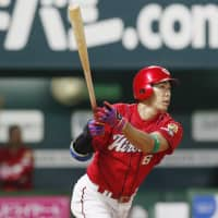Hiroshima's Tomohiro Abe belts a grand slam in the eighth inning. It was his second homer of the game. | KYODO