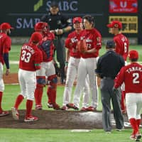 The Carp congregate on the mound as starting pitcher Aren Kuri (12) holds his cap in the fourth inning. | KYODO