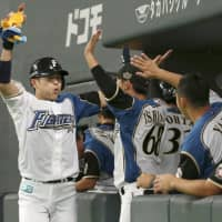 The Fighters' Yushi Shimizu returns to the dugout after hitting a home run against the Marines during the fourth inning on Wednesday in Sapporo. | KYODO