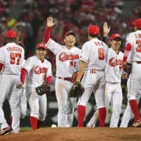 Hiroshima's Seiya Suzuki (51) and his Carp teammates celebrate their 5-1 victory over the Yomiuri Giants in Game 3 of the Central League Climax Series Final Stage on Friday night at Mazda Stadium. With the win, Hiroshima advanced to the Japan Series. | KYODO