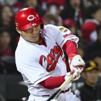 Seiya Suzuki drives in two runs for the Carp in the fifth inning of their Japan Series Game 2 win over the Hawks on Sunday at Mazda Stadium. | KYODO