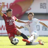 Kashima's Yasushi Endo (left) and Frontale's Shintaro Kurumaya contend for the ball on Sunday at Kashima Stadium. The game ended in a scoreless draw. | KYODO