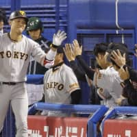 The Giants' Hayato Sakamoto is congratulated by teammates after hitting a go-ahead solo homer in the third inning against the Swallows on Saturday night in Game 1 of the Central League Climax Series first stage at Jingu Stadium. Yomiuri defeated Tokyo Yakult 4-1. | KYODO