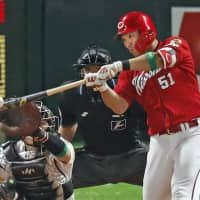 Seiya Suzuki hits a solo home run for the Carp in the sixth inning of Game 3 of the Japan Series on Tuesday in Fukuoka. | KYODO