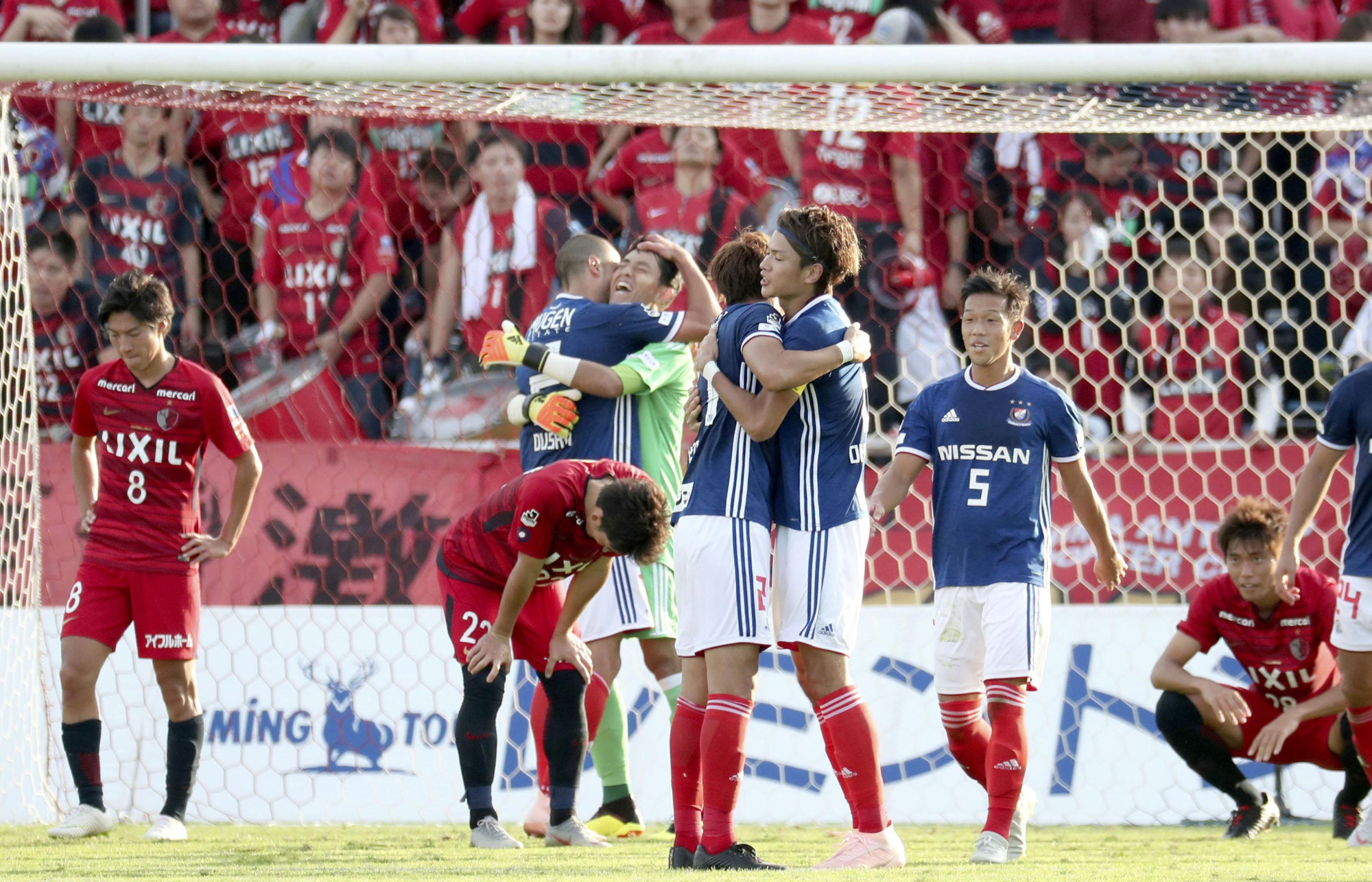 Yokohama F. Marinos players celebrate after the final whistle at Nippatsu Mitsuzawa Stadium on Sunday. The team clinched an appearance in the Levain Cup final with a 2-2 draw against Kashima Antlers. | KYODO