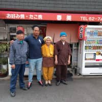 Harumi Okuno (second from right) and husband Hiroshi (left) pose with retired player Toetu'u Taufa outside their restaurant in Higashiosaka. | ANDREW MCKIRDY