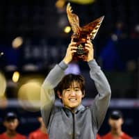 Yoshihito Nishioka lifts the trophy after winning the Shenzhen Open on Sunday in Guangdong, China. | AFP-JIJI
