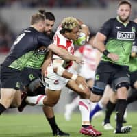 Japan's Lomano Lava Lemeki carries the ball against the World XV squad in Friday's match at Hanazono Rugby Stadium. The World XV topped the Brave Blossoms 31-28. | KYODO