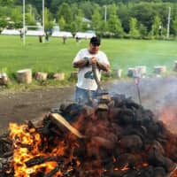 Stones are heated in a fire to lay a hangi, a traditional Kiwi meal, at the Jozankei club grounds in Sapporo in July. | HOKKAIDO BARBARIANS / VIA KYODO