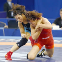 Risako Kawai (left) grapples with China's Pei Xingru in their women's 59-kg semifinal match on Monday. | KYODO