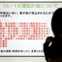 A woman is silhouetted against a screen showing trains that were halted due to Typhoon Trami at JR Sapporo Station in the city on Monday morning.  | KYODO