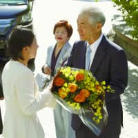 Tasuku Honjo, a professor at Kyoto University who jointly won this year's Nobel Prize in medicine, receives flowers at the university Tuesday morning accompanied by his wife, Shigeko.  | KYODO