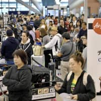 People wait in the crowded departures lobby of the international terminal at Kansai airport in Osaka Prefecture on Monday after Typhoon Trami passed through the region.  | KYODO