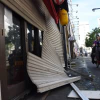 Storefront shutters are seen damaged in Tokyo's Suginami Ward on Monday after Typhoon Trami brought strong winds to the Kanto area.  | SATOKO KAWASAKI