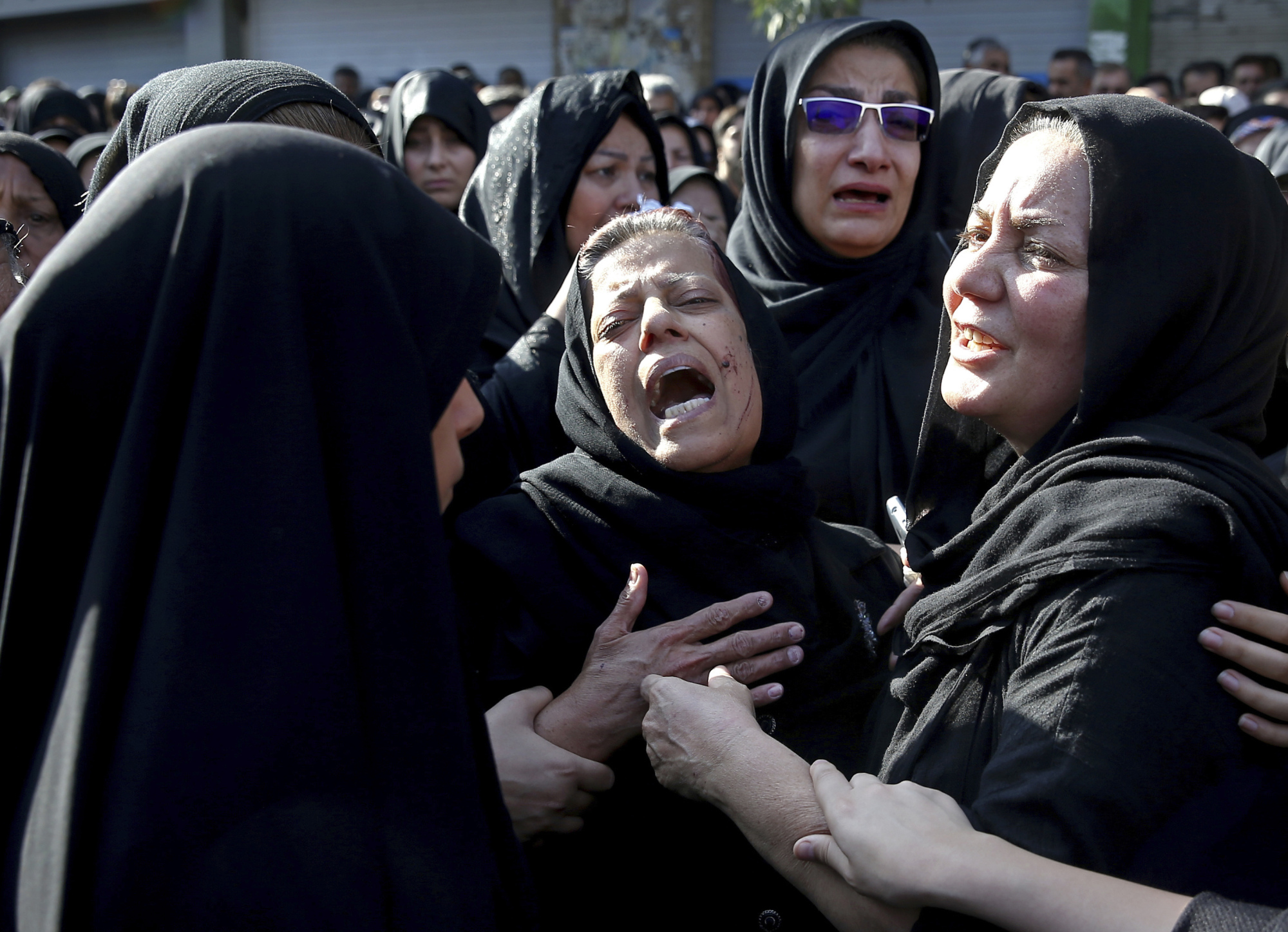 Families of victims of a terrorist attack on a military parade that killed 25 in the southwestern Iranian city of Ahvaz mourn at a mass funeral ceremony on Sept. 24. | AP