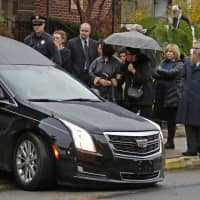 Mourners watch as the hearse carrying the casket of Richard Gottfried leaves the Ralph Schugar Funeral home in Pittsburgh following a memorial service Thursday. Mr. Gottfried, 65, was one of the 11 people killed while worshipping when a gunman opened fire at the Tree of Life Synagogue on Oct. 27. | AP
