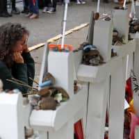 Anat Halevy Hochberg, of Brooklyn, New York, on Thursday visits a makeshift memorial outside the Tree of Life synagogue where 11 people were killed on Oct. 27 while worshipping, in the Squirrel Hill neighborhood of Pittsburgh. | AP