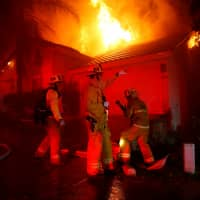 Firefighters battle flames overnight during a wildfire that burned dozens of homes in Thousand Oaks, California, on Friday. | REUTERS