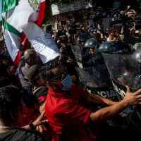 Mexican residents clash with police while protesting the arrival of Central American migrants in Tijuana, Mexico, on Sunday. President Trump tweeted that the migrant caravan is 'causing crime and big problems in Mexico,' and that the U.S. will not stand for the invasion.   BLOOMBERG