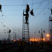 Workers are seen in silhouette at the Korla railway station under construction in Bayingolin Mongol Autonomous Prefecture, Xinjiang Uighur Autonomous Region, China, Oct. 31. | REUTERS