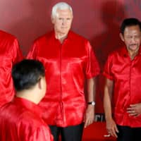 U.S. Vice President Mike Pence looks at Chinese President Xi Jinping as they prepare for a group photo with Asia-Pacific Economic Cooperation forum leaders at a gala dinner during the APEC summit in Port Moresby on Saturday. | REUTERS