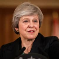 May vows to carry on as Brexit's hard-liners try to topple her