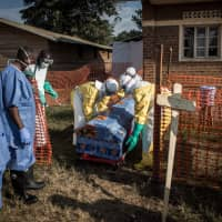 Medical workers disinfect the coffin of a deceased unconfirmed Ebola patient inside an Ebola Treatment Center run by The Alliance for International Medical Action (ALIMA) in August  in Beni, Congo. | AFP-JIJI