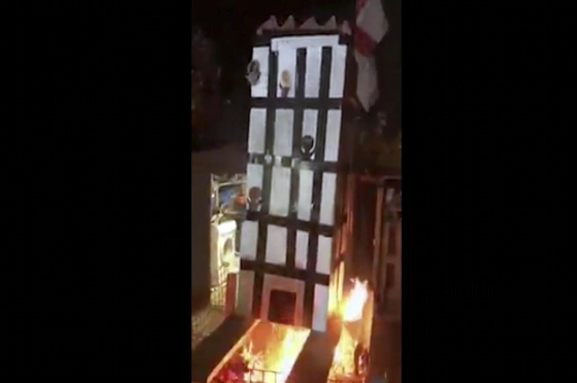 In this grab taken from video made available on Tuesday, people place a model of Grenfell Towers onto a bonfire, in London.   UGC / VIA AP