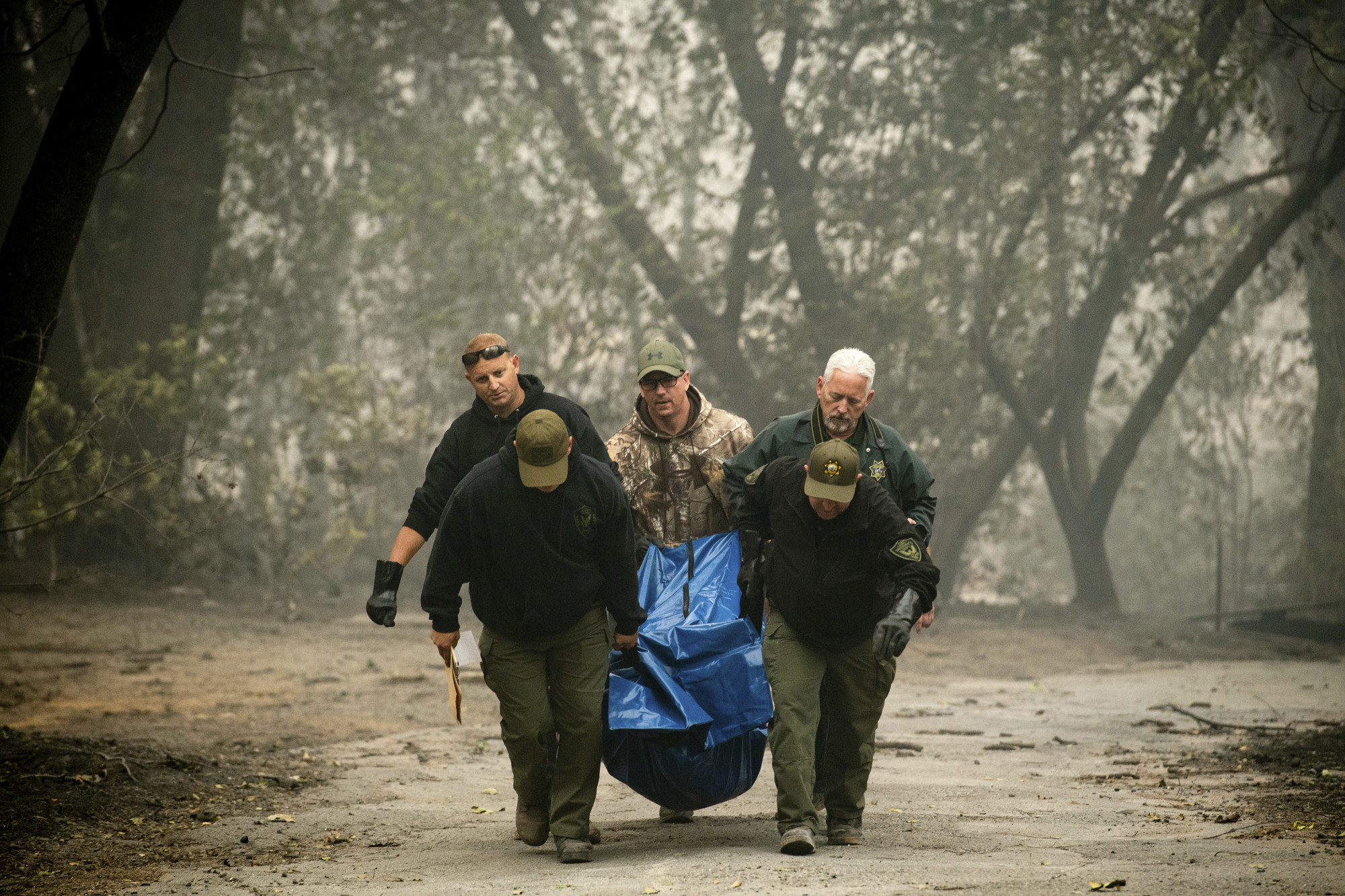 Sheriff's deputies recover the remains of a victim of the Camp Fire on Saturday in Paradise, California. | AP