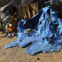 Melted recycling and trash containers stand next to one of at least 20 homes destroyed just on Windermere Drive in the Point Dume area of Malibu, California, on Saturday. Known as the Woolsey Fire, it has consumed thousands of hectares and destroyed dozens of homes. | AP