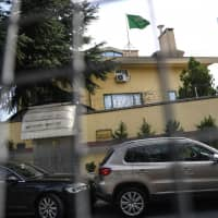The Saudi Arabia flag flies on the top of the consulate as diplomatic vehicles wait outside the Saudi Consulate on Thursday in Istanbul. Journalist Jamal Khashoggi was strangled as soon as he entered the consulate and his body was dismembered and destroyed as part of a premeditated plan, Turkey's chief prosecutor said on Wednesday, making details of the murder public for the first time. | AFP-JIJI