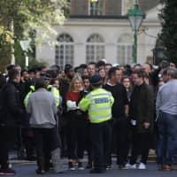 Staff evacuated from the office building housing Sony Music's offices are seen with police officers on a nearby street after an incident at the offices in London on Friday. | AFP-JIJI