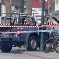 A burnt out vehicle is surrounded by police tape on Bourke Street in central Melbourne, Australia, on Friday. | AAP / VIA REUTERS