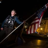 A man holding an upside-down U.S. flag participates in a protest against U.S. President Donald Trump's alleged interference in the investigation headed by Robert Mueller in Washington on Thursday. | AFP-JIJI