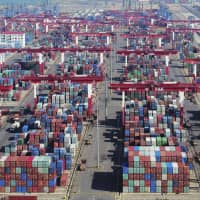 Containers are piled high at a port in Qingdao in eastern China's Shandong province on Thursday. | CHINATOPIX / VIA AP