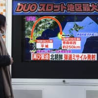 A pedestrian watches a screen broadcasting a map of Japan and the Korean Peninsula during a news program reporting on North Korea's missile launch, in Tokyo on Nov. 29 last year.   BLOOMBERG