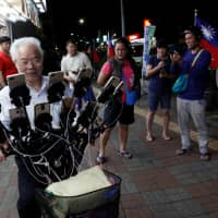 Neighbors watch Chen San-yuan, 70, known as 'Pokemon grandpa,' as he plays the mobile game 'Pokemon Go' near his home with 15 mobile phones, in a Taipei suburb on Monday. | REUTERS