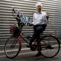 Chen San-yuan, 70, known as 'Pokemon grandpa,' poses with his bicycle as he plays the mobile game 'Pokemon Go' near his home with 15 mobile phones, in a Taipei suburb on Monday. | REUTERS