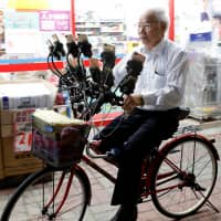 Chen San-yuan, 70, known as 'Pokemon grandpa,' rides his bicycle as he plays the mobile game 'Pokemon Go' near his home with 15 mobile phones, in a Taipei suburb on Monday. | REUTERS