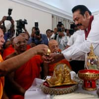 Sri Lanka's newly appointed prime minister, Mahinda Rajapaksa, is blessed by Buddhist monks during the ceremony to assume duties at the prime minister's office in Colombo on Monday. | REUTERS