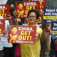 Protesters display placards during a rally held outside the Chinese Consulate in the Makati  financial district, east of Manila, on Wednesday. | AP