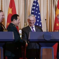 U.S. Secretary of State Mike Pompeo, Chinese Defense Minister Gen. Wei Fenghe (second from left), U.S. Secretary of Defense Jim Mattis and Chinese Politburo member Yang Jiechi shake hands at the conclusion of a news conference at the State Department in Washington on Friday. | AP