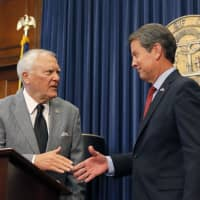 Republican Brian Kemp (right) shakes hands with Georgia Gov. Nathan Deal at the Capitol on Thursday in Atlanta. Kemp resigned Thursday as Georgia's secretary of state, a day after his campaign said he's captured enough votes to become governor despite his rival's refusal to concede. | BOB ANDRES / ATLANTA JOURNAL-CONSTITUTION / VIA AP
