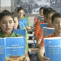 Young Muslims read from official Chinese-language textbooks in classrooms at the Hotan Vocational Education and Training Center in Hotan, in northwest China's Xinjiang region, in this file image from undated video footage. | AP
