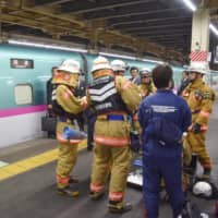 Firefighters are seen near a bullet train at Omiya Station in Saitama Prefecture on Friday. Smoke coming from a mobile battery carried by a passenger halted operations on the line. | KYODO