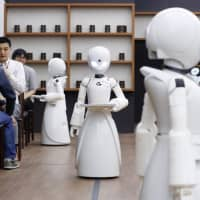 OriHime-D humanoid robots remotely controlled from home by workers with severe physical disabilities serve customers at a cafe in Minato Ward, Tokyo, on Monday. The cafe will operate through Dec. 7 on a trial basis. | KYODO