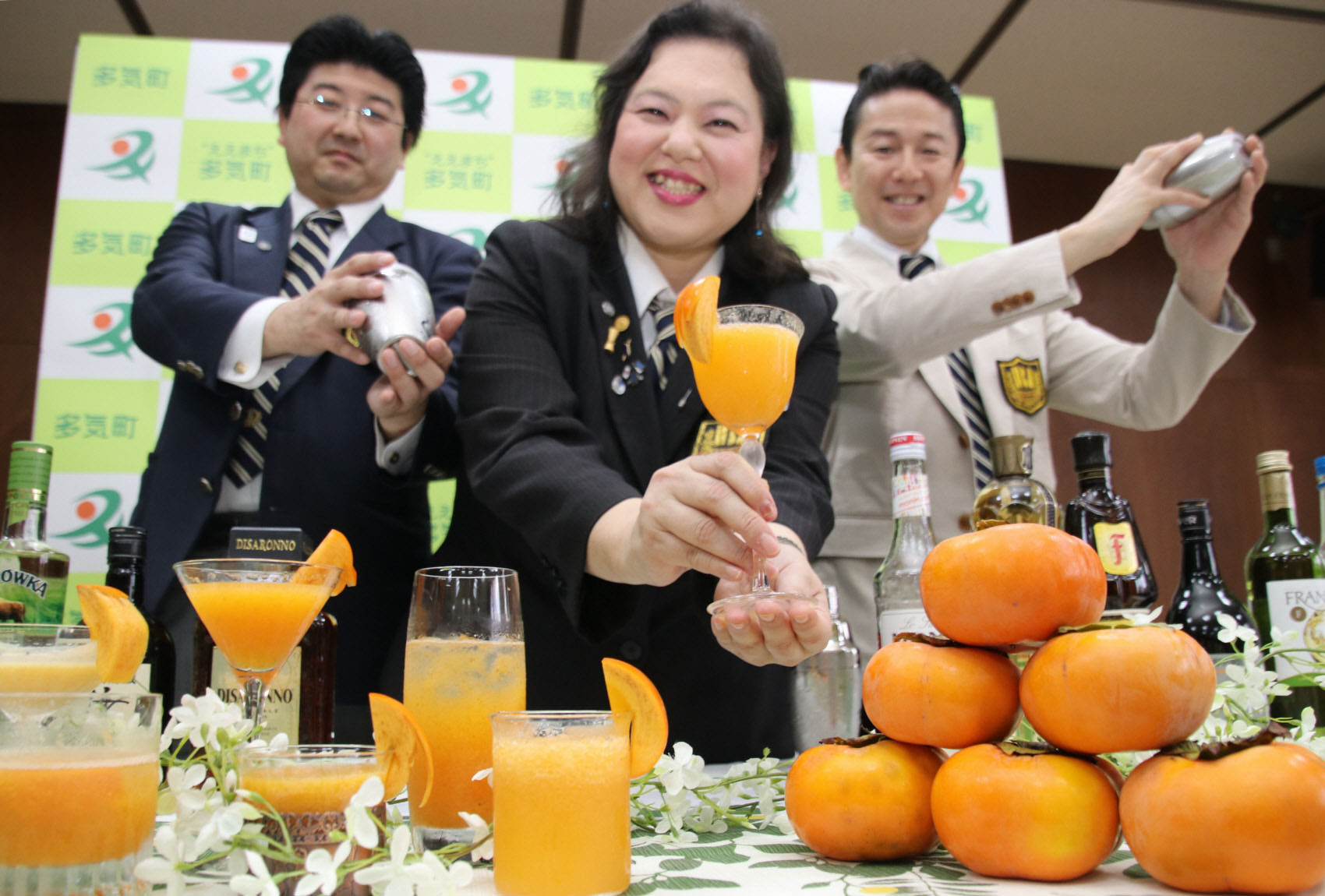 Members of the Nippon Bartenders Association's branch in Mie Prefecture show off cocktails made from unshipped Jiro persimmons at a tasting event at the Taki Municipal Government building on Nov. 6. | CHUNICHI SHIMBUN